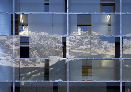 cube hotel glass facade reflecting mountains
